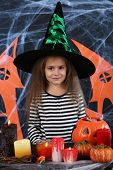 Little girl Witch in hat on Halloween decorations background