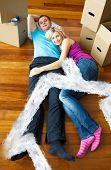Cute couple sleeping on the floor against house outline in clouds