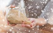 cooking, people and home concept - close up of female emptying jar with quinoa in kitchen