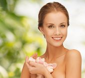 beauty, people and health concept - beautiful smiling young woman with flowers and bare shoulders over green background