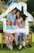 Smiling multi generation family sitting on bench in park against house outline in clouds