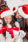 Festive mother and daughter exchanging gifts against twinkling stars