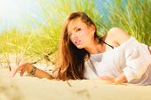 image of dune grass  - Young woman female model posing outdoor on background of dunes sky and grass - JPG