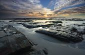 foto of ares  - The light from the sun filtered through high cloud just after sunrise falls across the rocks wet sand and shallow tidal flows at Plantation Point Vincentia in Jervis Bay creating interesting ares of light and dark - JPG