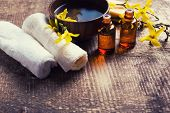 image of massage oil  - Spa setting. Essential aroma oil water in bowl towels yellow flowers on aged wooden background. Selective focus. Place for text. Toned image.