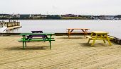 picture of lumber  - Four colorful picnic benches on a dock of treated lumber at a marina - JPG