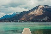 foto of pier a lake  - Pier on the mountain lake with city on background - JPG