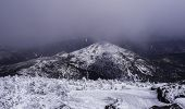 image of snow clouds  - Clouds breaking over a snow covered mountain peak
