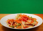 foto of green papaya salad  - thai hot papaya salad with a green background on a wood table top - JPG