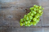 stock photo of testis  - Bunch of ripe tasty sweet green grapes on old wooden background - JPG