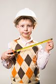 stock photo of boy scouts  - Boy in a white construction helmet and a tape measure in hand - JPG