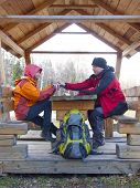 pic of gazebo  - Man and woman sitting in a wooden gazebo in the woods and drink from a thermos hot drink - JPG