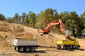 foto of dump_truck  - Large track hoe excavator filling a dump truck with rock and soil for fill at a new commercial development road construction project - JPG