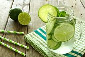 stock photo of masonic  - Detox water with lime and cucumbers in a mason jar on a wood table with checkered cloth and straws - JPG