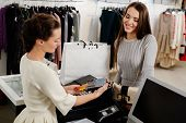 stock photo of showrooms  - Happy woman customer paying with credit card in fashion showroom - JPG