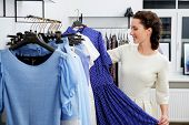 image of showrooms  - Young woman choosing clothes on a rack in a showroom  - JPG