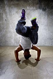 image of inverted  - Inverted black breakdancer doing a headstand or handstand or urban yoga - JPG