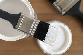 stock photo of paint pot  - Painting and decorating shallow focus top down view of a pot of white paint and brush - JPG