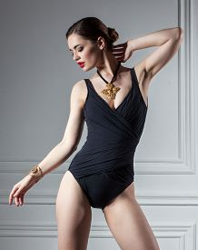 stock photo of monokini  - photo of elegance woman dancing in black swimsuit - JPG