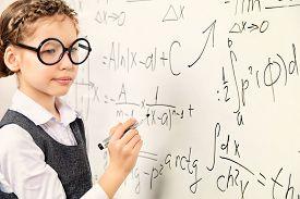 pic of schoolgirl  - Happy smart schoolgirl in big glasses performs the task at the blackboard - JPG