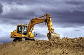 foto of heavy equipment operator  - Yellow excavator on a hill - JPG
