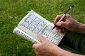 stock photo of brain teaser  - Woman doing a Sudoku puzzle with a pencil in hand - JPG