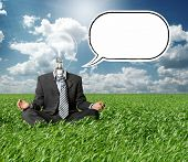 businessman in lotus pose and lamp-head with thought bubble in green grass on blue summer sky
