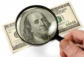 Hundred dollar bill under a magnifying glass is being inspected Conceptual photo isolated on white b