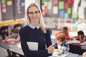 Portrait of happy teacher standing with arms crossed in classroom at school poster