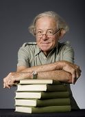 Waist-up view of mature intellectual man with stack of books. Studio photo.