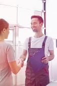 Smiling automobile mechanic shaking hands with female customer in automobile repair shop poster