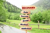 Rehabilitation concept. Wooden signboards pointing different directions to RECOVERY and ADDICTION on poster