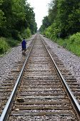 stock photo of train track  - Young boy walking on lonely railroad tracks - JPG