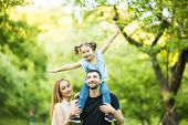 Young Happy Family Of Three Having Fun Together Outdoor. Pretty Little Daughter On Her Father Back. poster