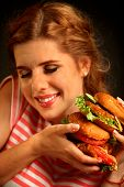 Woman eating burger and winks. Portrait of happy student going to seductively eat great sandwich for poster