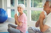 Senior couple performing yoga on exercise mat at home poster