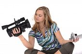 Young pretty woman with professional and amateur camcorders