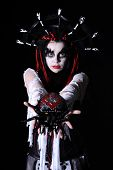 portrait of woman with voodoo shaman make-up hold toy spider isolated on black