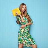 Blonde Young Woman In Floral Spring Summer Dress. Girl Posing On A Blue Background. Summer Floral Ou poster