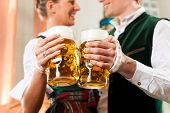 Man and woman with beer glasses in Bavarian tracht in brewery in front of a brew kettle