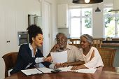 Front view of a female African American  real estate agent and senior couple discussing over documen poster