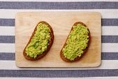 Guacamole Sandwich On Light Background. Avocado Sandwiches On Wooden Board And Textile Top View poster