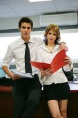 Two young business people with folders