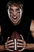 American football player screaming aggressive holding american football on black background. Strong fit Caucasian fitness man.