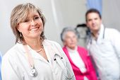 stock photo of geriatric  - Geriatric female doctor smiling with an elder patient at the hospital - JPG