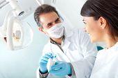 Dentista mostrando uma mulher como escovar seus dentes na prótese