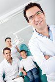 Pediatra dentista masculina com sua equipe e um paciente jovem
