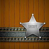 Emblema do xerife com elemento de jeans em um fundo de madeira.