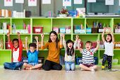 Happy Asian Female Teacher And Mixed Race Kids In Classroom,kindergarten Pre School Concept poster