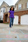 image of hopscotch  - Child playing hopscotch outside at her home - JPG